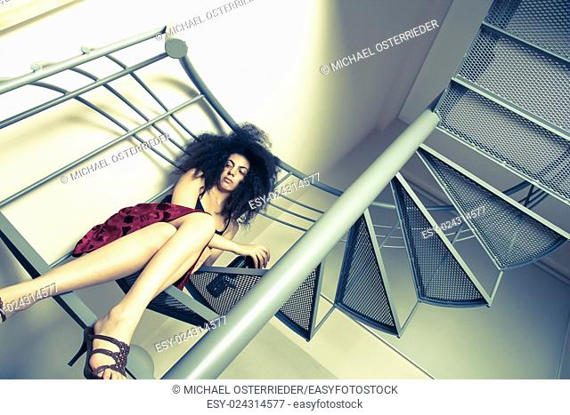 A young brazilian woman sitting on the stairs with a glass of red wine
