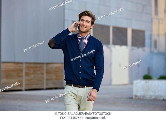 Young businessman talking smartphone phone walking on the street