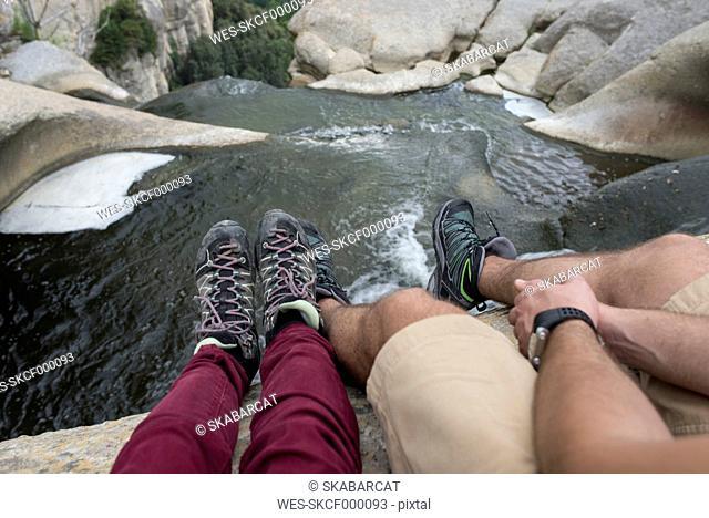 Spain, Catalonia, couple sitting at Salt de Sallent waterfall