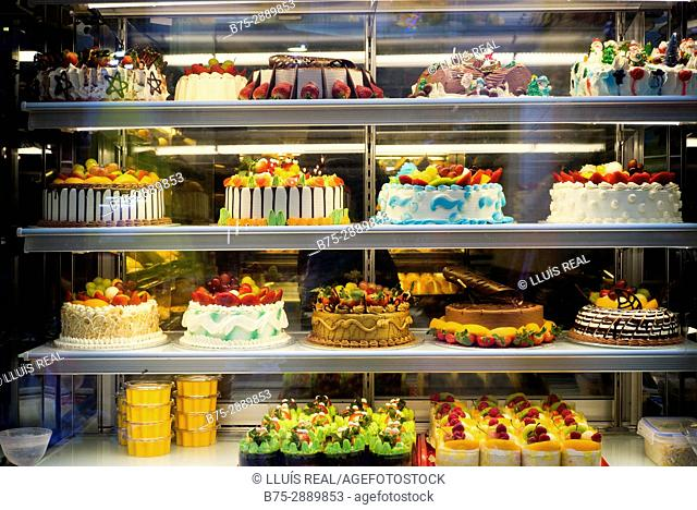 Display of cakes in a sweet shop in China Town, London, England, UK