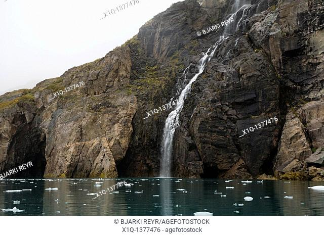 Waterfall falling into a fjord, small packs of ice floating around  Bredefjord near Narsarsuaq, South Greenland