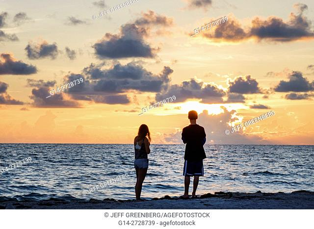 Florida, Gulf of Mexico, Gulf Coast, Anna Maria Island, Bradenton Beach, beachfront, sunset, ocean, water, man, girl, boy, teen, couple, silhouette, clouds