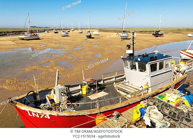 A fishing boat in the harbour at Wells-next-the-sea , Norfolk , England , Britain , Uk