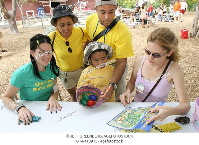 Easter Seals volunteers with map and Hispanic family. Easter Egg Hunt. Parrot Jungle Island. Miami. Florida. USA