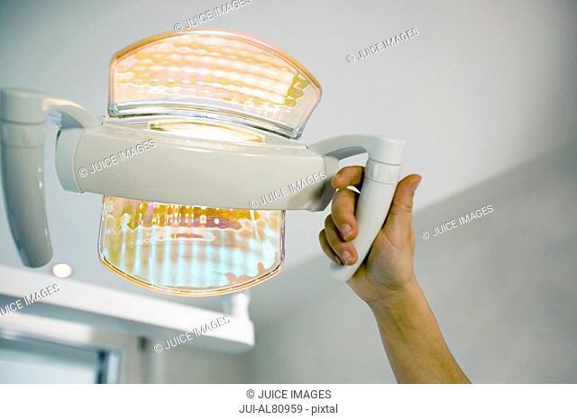 Dentist adjusting dental light