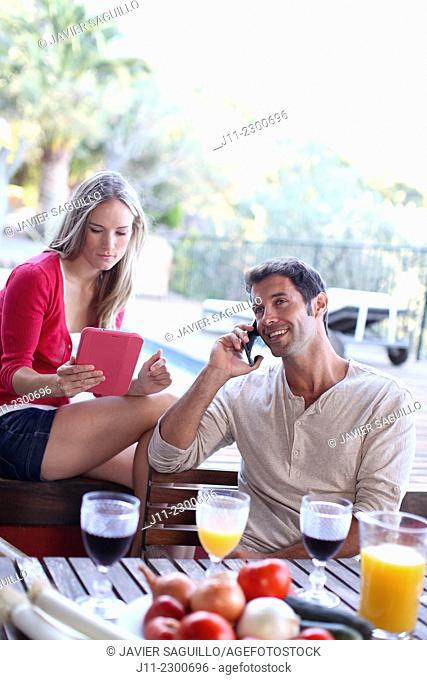 Couple with cell phone and digital tablet