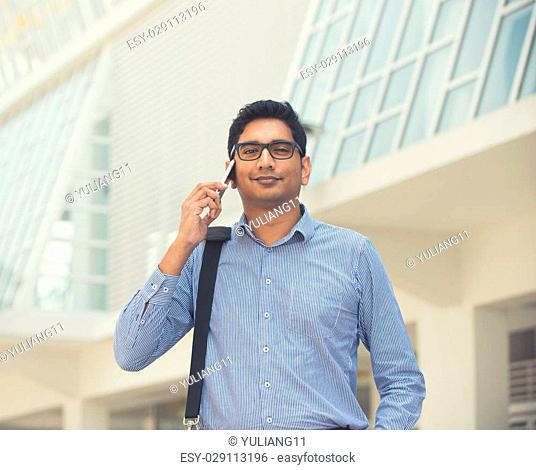 young indian business man on a phone conversation light vintage tone