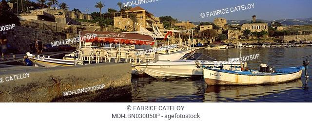 Byblos - The harbour and its fishing boats. In the background the Bab El Mina restaurant with its white curtains