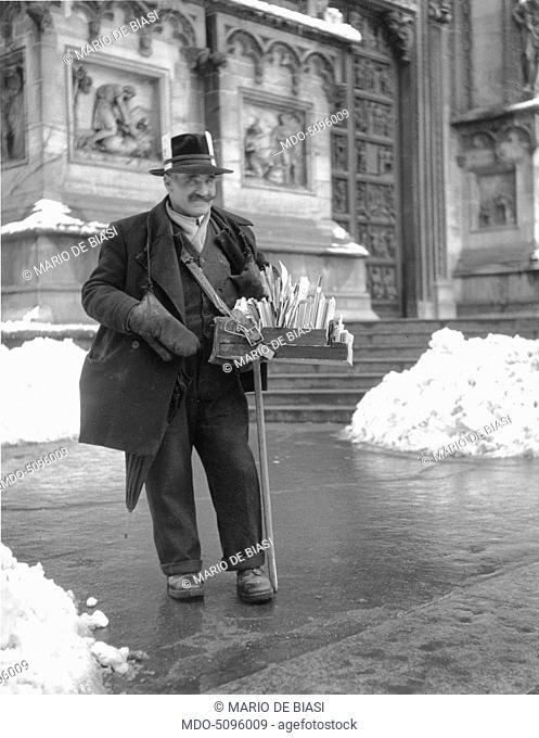A postcard seller in Piazza del Duomo. Milan, 1950s