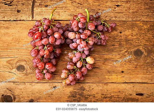 bunch of fresh grapes on wooden kitchen bench