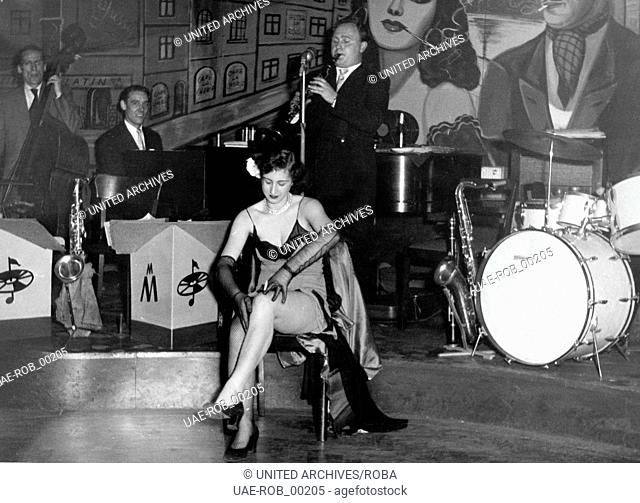 Ein Tänzerin bei ihrem Auftritt in einem Nachtclub auf der Reeperbahn in Hamburg, 1950er Jahre. A female dancer performing on stage of a nightclub at Hamburg...