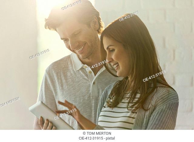 Smiling couple using digital tablet