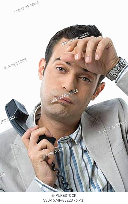 Businessman holding a telephone receiver with his hand on his forehead
