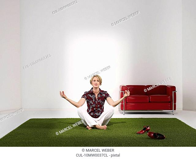 Woman meditating in green office