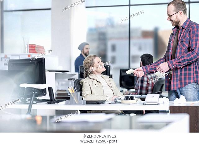 Man handing over note to female coworker in office