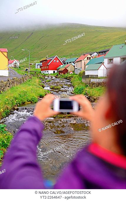 Young woman taking photos with mobile in village of Gjógv, Eysturoy, Faroe Island
