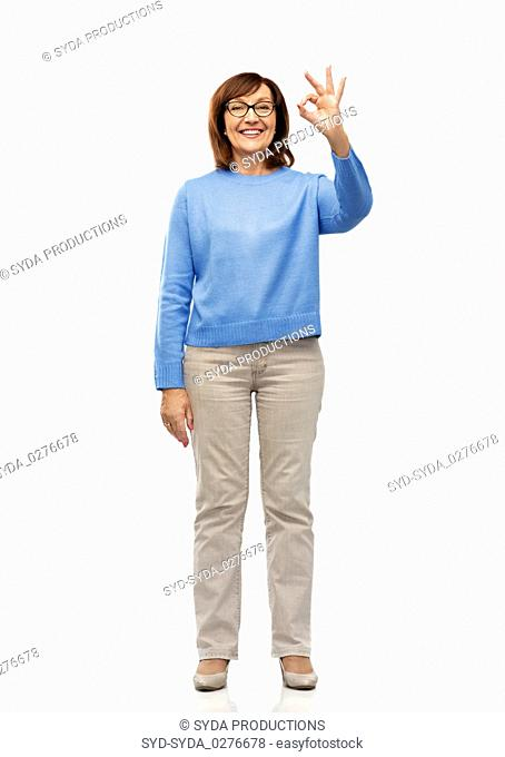 happy senior woman in glasses showing ok hand sign