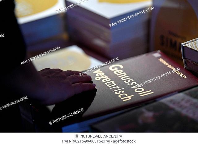 "14 February 2019, Berlin: 69th Berlinale: One hand holds a book entitled """"Genussvoll vegetarisch"""" by Israeli-British chef Yotam Ottolenghi"