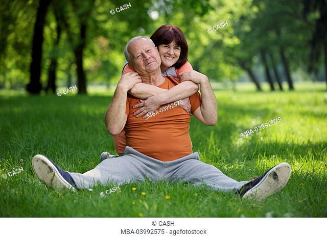 older couple, sports wear, meadow, sitting, happy, embrace