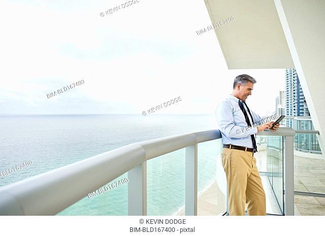 Caucasian businessman using digital tablet on balcony