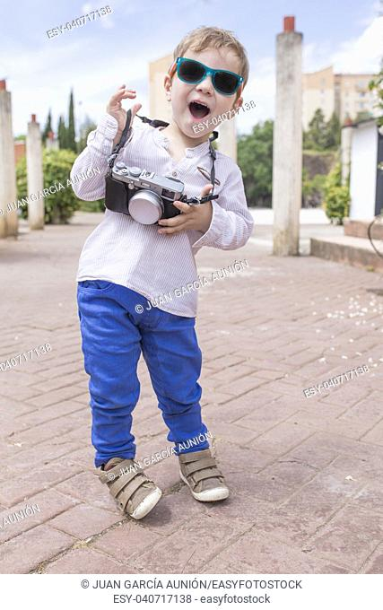 Cute happy boy with vintage photo camera as a little tourist at park. Tourism with children concept