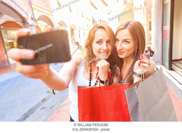 Girlfriends taking selfie while shopping in town