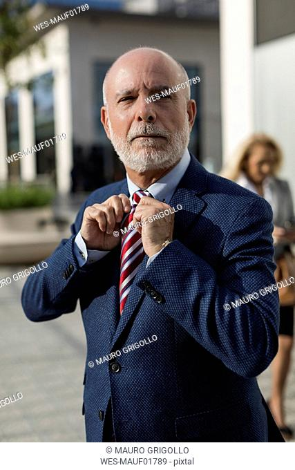 Senior businessman adjusting his tie with businesswoman in background
