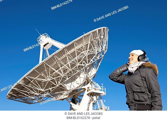 Hispanic technician listening to satellite under blue sky