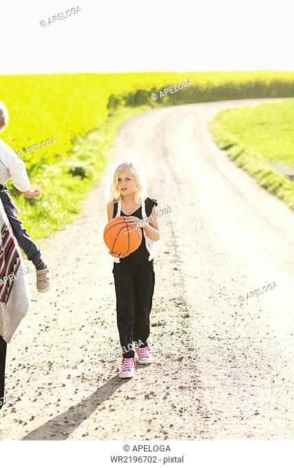 Girl holding basketball while walking on dirt road at rapeseed field
