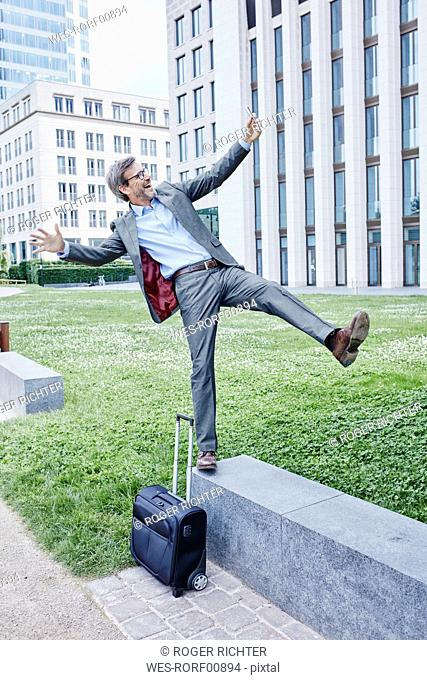 Playful mature businessman with rolling suitcase balancing on wall taking a selfie