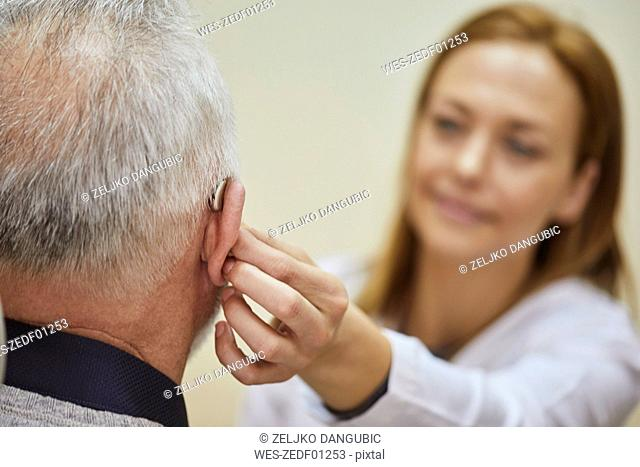 Female doctor applying hearing aid to senior man's ear