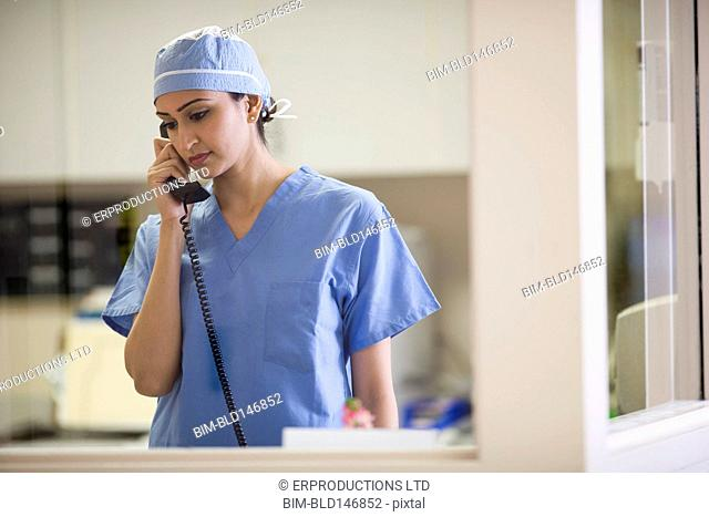Asian doctor talking on telephone in hospital