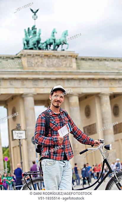 Tourist with bike and guide book in Brandenburg Gate, Berlin, Germany