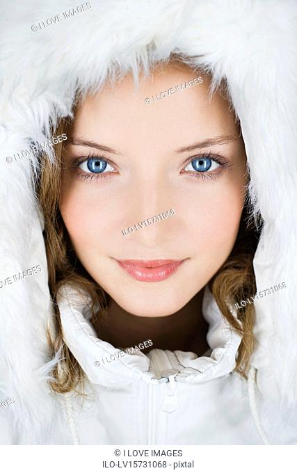A young woman wearing a winter coat with a fur hood , close-up