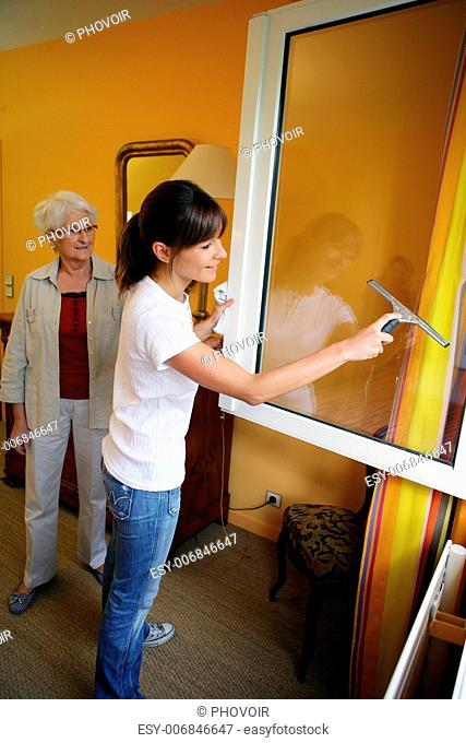 Young woman helping senior woman doing chores