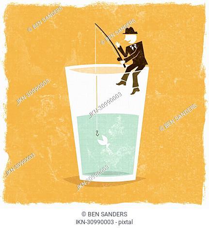 Businessman fishing on edge of glass