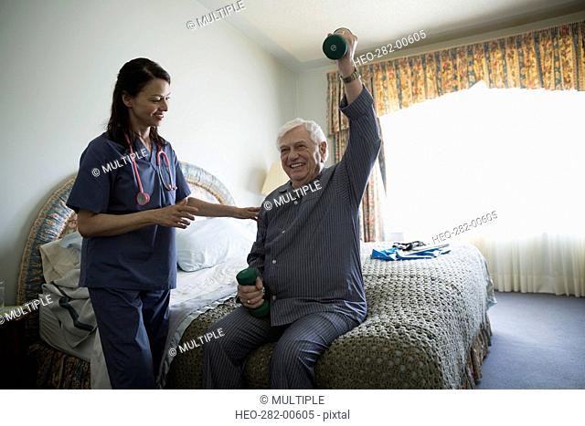 Home caregiver helping senior man lifting weights