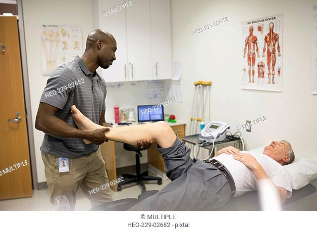 Physical therapist stretching patient leg