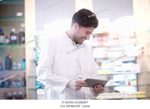 Young male pharmacist using digital tablet in pharmacy