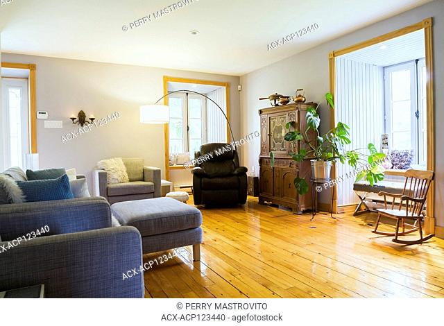 Grey upholstered armchair and sofa plus brown leather armchair, antique wooden buffet, green plant and rocking chair in living room with pinewood floorboards...