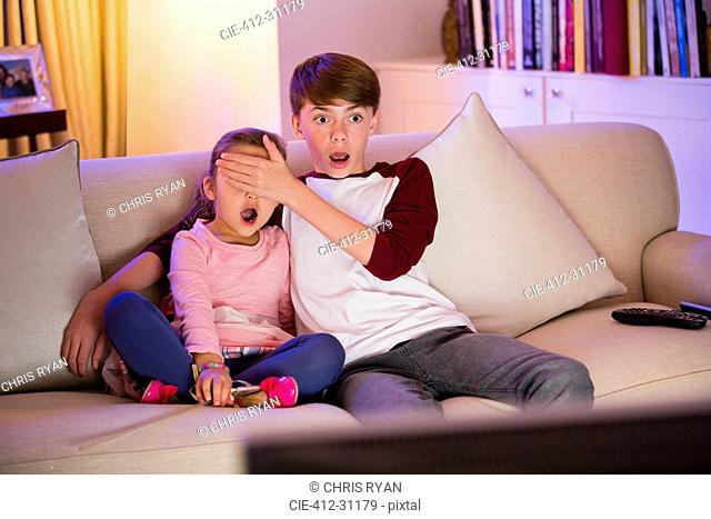 Brother covering surprised sister's eyes watching TV in living room