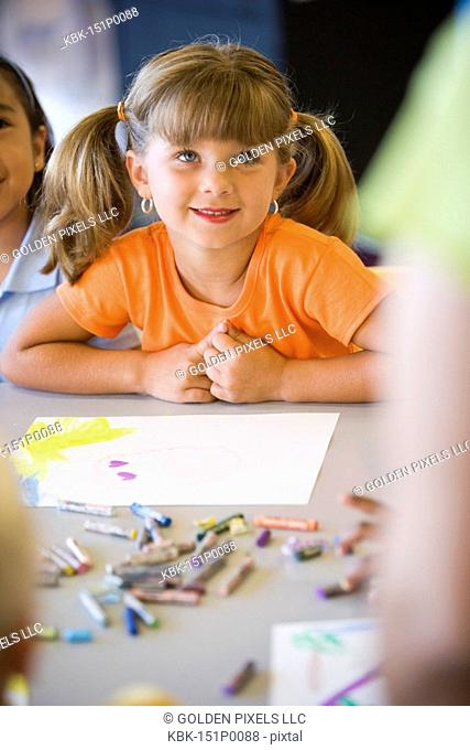 Close up of little girl looking up at teacher in class