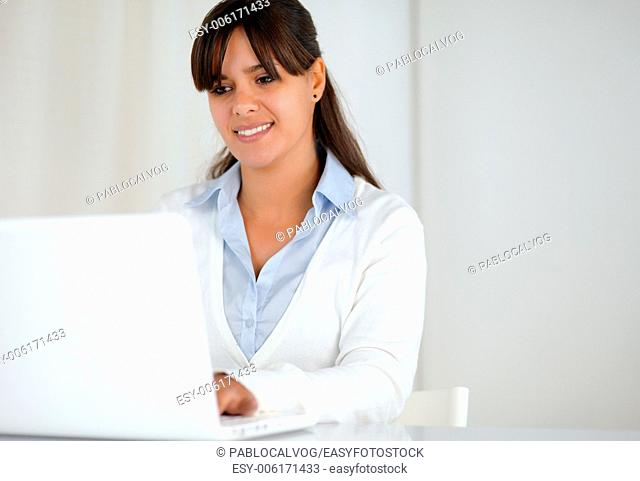 Portrait of a smiling young woman working on laptop computer - copy space