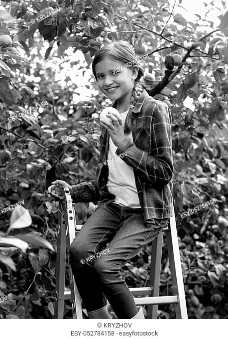 Black and white portrait of beautiful smiling girl sitting on stepladder and biting fresh apple