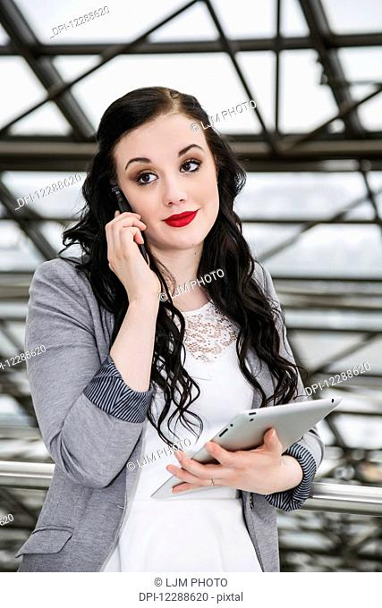 Attractive young millennial business woman on her cell phone in downtown office building; Edmonton, Alberta, Canada