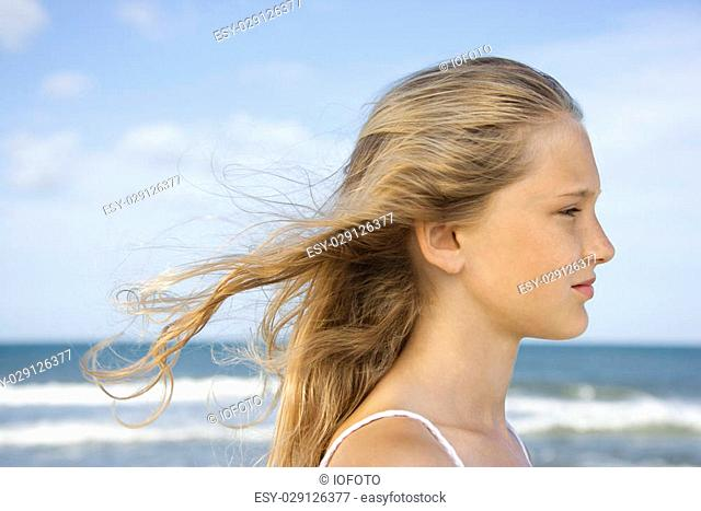 Caucasian pre-teen girl on beach with hair blowing in wind