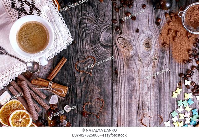 Grey wooden background with black coffee and a variety of sweets, empty space in the middle