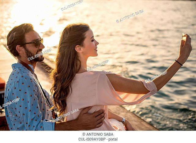 Romantic couple taking smartphone selfie on boat at Dubai marina, United Arab Emirates