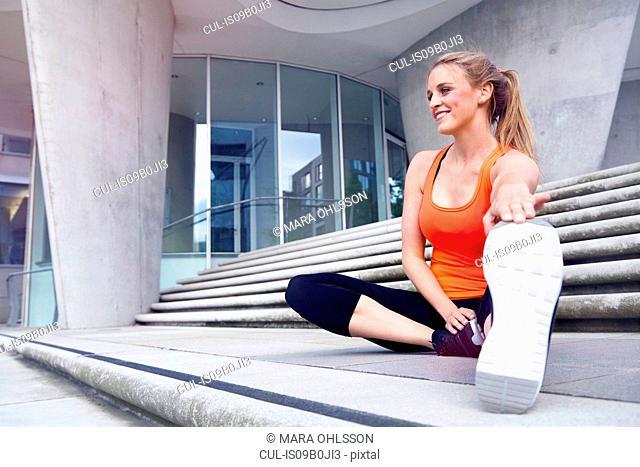 Woman sitting on steps stretching leg
