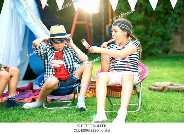 Girl and two brothers eating ice lollies in front of homemade tent in garden